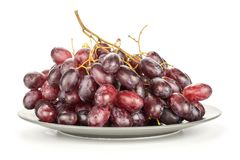 Fresh raw red wine grapes isolated on white. Red globe grape cluster on a grey plate isolated on white background fresh shiny dark pink berries Royalty Free Stock Photo
