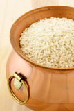 Fresh raw risotto on copper pot. Raw arborio rice used to make risotto, one of the most famous and delicious  Italian dishes Stock Image