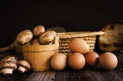 Fresh raw royal champignons and eggs on dark wooden rustic table. Royalty Free Stock Photos
