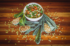 Fresh raw salad on wooden table. Fresh healthy salad in white bowl with kale leafs and nuts on wooden table. Healthy food concept. Image has vintage filter Royalty Free Stock Images