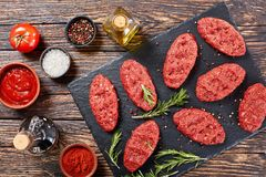 Fresh raw salisbury beef steaks, close-up. Fresh raw salisbury beef steak on black stone plate with rosemary and peppercorn, bottle of olive oil, spices sauces Royalty Free Stock Photo