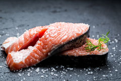 Fresh raw salmon with coarse salt. On black rock Royalty Free Stock Images