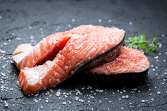 Fresh raw salmon with coarse salt. On black rock Royalty Free Stock Photography