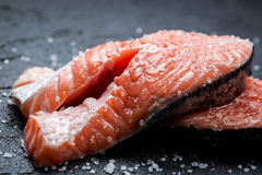 Fresh raw salmon with coarse salt. On black rock Stock Photos