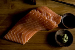 Fresh raw salmon on cutting board. Raw fresh fatty salmon on cutting board with green wasabi and soy sauce in wooden small cups Stock Image