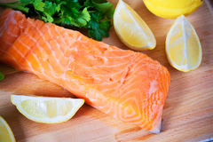 Fresh raw salmon on cutting board. Selective focus. Fresh raw salmon and lemons on cutting board. Selective focus Royalty Free Stock Images