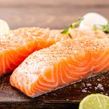 Fresh raw salmon fillet. With aromatic herbs, spices on old wooden background Stock Image