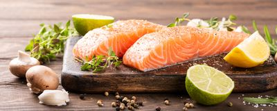 Fresh raw salmon fillet. With aromatic herbs, spices on old wooden background with copy space. Banner Stock Photo