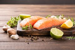 Fresh raw salmon fillet. With aromatic herbs, spices on old wooden background with copy space Royalty Free Stock Images