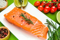 Fresh raw salmon fillet with aromatic herbs, spices. Tomatos, rosemary, lime Royalty Free Stock Photography