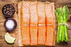 Fresh raw salmon fillet with asparagus and lime top view Royalty Free Stock Photos