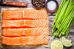 Fresh raw salmon fillet with asparagus and lime top view Royalty Free Stock Photo