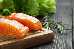 Fresh raw salmon fillet on cutting board. Fresh raw salmon fillet on cutting board with seasonings Royalty Free Stock Photo