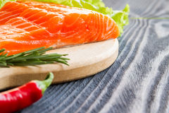 Fresh raw salmon fillet on cutting board. Fresh raw salmon fillet on cutting board with seasonings Stock Photos