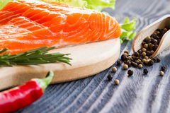 Fresh raw salmon fillet on cutting board. Fresh raw salmon fillet on cutting board with seasonings Royalty Free Stock Image