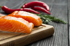 Fresh raw salmon fillet on cutting board. Fresh raw salmon fillet on cutting board with seasonings and vegetables Royalty Free Stock Photos