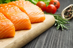 Fresh raw salmon fillet on cutting board. Fresh raw salmon fillet on cutting board with seasonings and vegetables Stock Photography