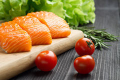Fresh raw salmon fillet on cutting board. Fresh raw salmon fillet on cutting board with seasonings and vegetables Royalty Free Stock Image