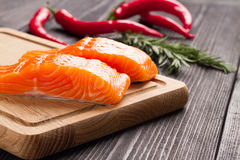 Fresh raw salmon fillet on cutting board. Fresh raw salmon fillet on cutting board with seasonings and vegetables Royalty Free Stock Photography