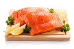 Fresh raw salmon fillet on cutting board. On white background Stock Photos