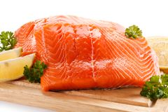 Fresh raw salmon fillet on cutting board. On white background Royalty Free Stock Image
