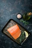Fresh raw salmon filet. Fresh raw salmon fillet on dark stone background, top view with copy space Stock Images
