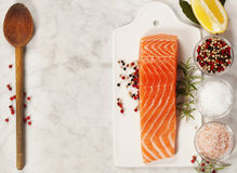 Fresh raw salmon fillet. Delicious portion of fresh salmon fillet with aromatic herbs and spices - healthy food, diet or cooking concept. Top view Stock Photo