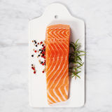 Fresh raw salmon fillet. Delicious portion of fresh salmon fillet with aromatic herbs and spices - healthy food, diet or cooking concept. Top view Royalty Free Stock Image