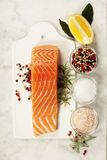 Fresh raw salmon fillet. Delicious portion of fresh salmon fillet with aromatic herbs and spices - healthy food, diet or cooking concept. Top view Royalty Free Stock Photo