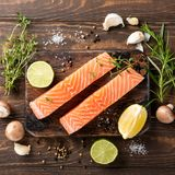 Fresh raw salmon fillet, flat lay. Flat lay with fresh raw salmon fillet and aromatic herbs, spices, pepper, salt, mushrooms lemon and rosemary. Old wooden Royalty Free Stock Photo