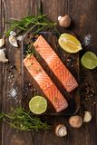 Fresh raw salmon fillet, flat lay. Flat lay with fresh raw salmon fillet and aromatic herbs, spices, pepper, salt, mushrooms lemon and rosemary. Old wooden Stock Photos