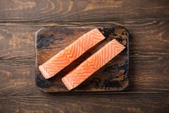 Fresh raw salmon fillet, flat lay. Flat lay with fresh raw salmon fillet. Old wooden background. Top view. Copy space Royalty Free Stock Images