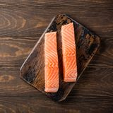 Fresh raw salmon fillet, flat lay. Flat lay with fresh raw salmon fillet. Old wooden background. Top view. Copy space Stock Photos