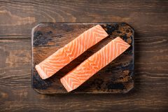 Fresh raw salmon fillet, flat lay. Overhead shoot of fresh raw salmon fillet. Old wooden background. Top view. Copy space Royalty Free Stock Images