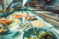 Fresh raw salmon fillet in the freezer of a modern restaurant. Fresh raw salmon fillet and various seafood exposed in the showcase freezer of a modern restaurant royalty free stock photo
