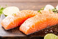 Fresh raw salmon fillet. With aromatic herbs, spices on old wooden background Royalty Free Stock Image