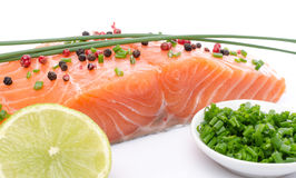 Fresh raw salmon fillet with herbs, lemon and spice. Isolated on white Stock Photos