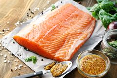Fresh raw salmon fillet with honey mustard marinade. On wooden table Stock Image