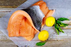 Fresh raw salmon fillet with and lemon. Fresh raw salmon fillet with lemon and ingredients for cooking on a wooden board Royalty Free Stock Photo