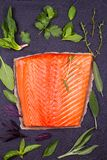 Fresh raw salmon fillet with lemon, lime, sage, mint, spinach, cilantro, thyme and rosemary. Healthy food concept on black backgro. Fresh raw salmon fillet with Stock Photo