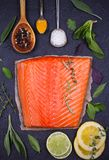 Fresh raw salmon fillet with lemon, lime, sage, mint, spinach, cilantro, thyme and rosemary. Healthy food concept on black backgro. Und. View from above, top Stock Image