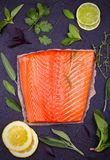 Fresh raw salmon fillet with lemon, lime, sage, mint, spinach, cilantro, thyme and rosemary. Healthy food concept on black backgro. Und. View from above, top Royalty Free Stock Photo