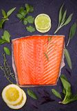 Fresh raw salmon fillet with lemon, lime, sage, mint, spinach, cilantro, thyme and rosemary. Healthy food concept on black backgro. Und. View from above, top Stock Images