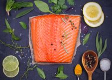 Fresh raw salmon fillet with lemon, lime, sage, mint, spinach, cilantro, thyme and rosemary. Healthy food concept on black backgro. Und. View from above, top Royalty Free Stock Image