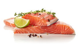 Fresh raw salmon fillet with lime, thyme, pepper and salt isolat. Ed on white background Royalty Free Stock Image