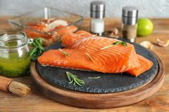 Fresh raw salmon fillet and marinade. On wooden table Royalty Free Stock Images