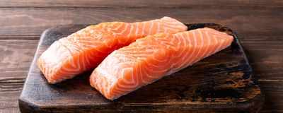 Fresh raw salmon fillet, flat lay. Fresh raw salmon fillet. Old wooden background. Banner selective focus Royalty Free Stock Images