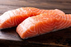Fresh raw salmon fillet, flat lay. Fresh raw salmon fillet. Old wooden background. Selective focus Royalty Free Stock Photo