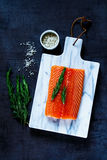 Fresh raw salmon. Fillet with rosemary and grey salt on marbre cutting board. Top view. Background layout with free text space. Healthy food, diet or cooking Stock Image