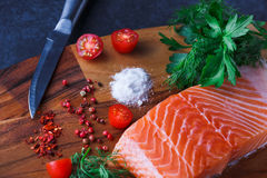 Fresh raw salmon fillet with spices. Raw salmon fillet and ingredients for cooking on a wooden cutting board Royalty Free Stock Photo